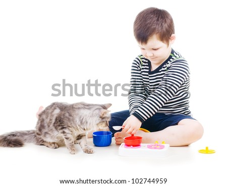 little boy feeding a cat with a toy spoon