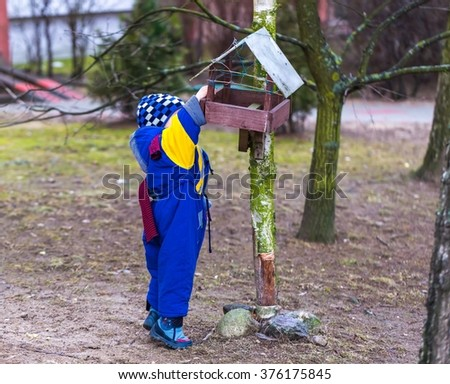Little boy feeds birds outdoor on city park at early springtime. Happy 2 years old child throwing something to eat to bird feeder. - stock photo