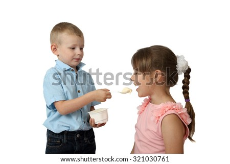 Little boy feeds girl by yogurt with focus on girl and spoon isolated on white background