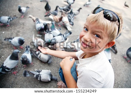 Little boy feeds pigeons with palm, closeup, Barcelona, Spain