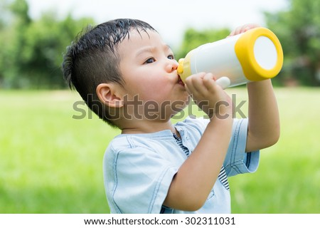 Little boy feeling thirsty and drink with water bottle - stock photo