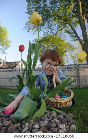 Little boy finds an egg during an Easter egg hunt - stock photo