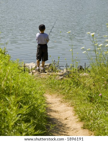 Little boy fishing on the lake - stock photo