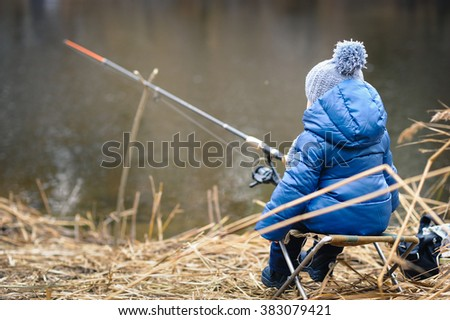 Little boy fishing on the river bank - stock photo