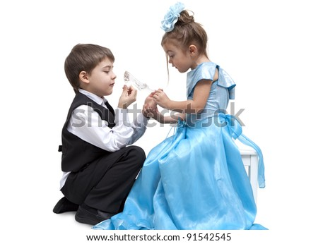 Little boy fitting a glass slipper onto a beautiful little girl - stock photo