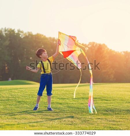 Little boy flies a kite over sunset - stock photo