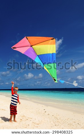 Little boy flying a kite on tropical beach - stock photo