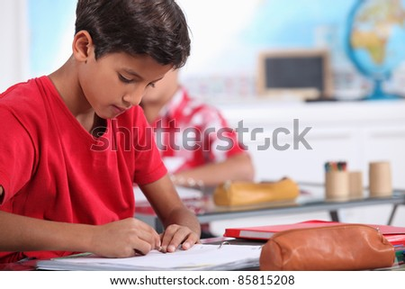 little boy focusing on his work in classroom - stock photo