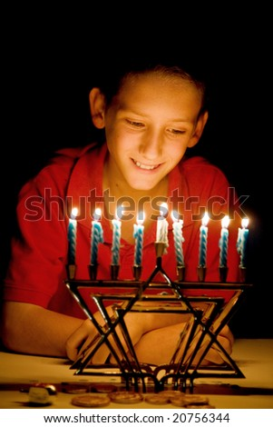 Little boy gazing on a lighted menorah, illuminated only by its light.  Shallow depth of field with focus on boy's eyes. - stock photo