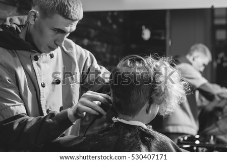 Little Boy Getting Haircut By Barber While Sitting In Chair At Barbershop. Barbershop Theme