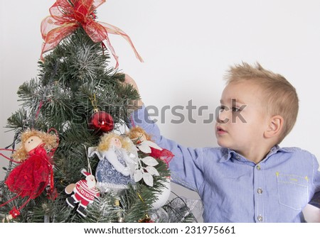 little boy getting ready for the new year and decorates a Christmas tree - stock photo