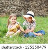Little boy gives flowers to the little girl near the country house - stock photo