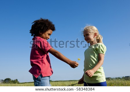 Little boy giving a flower to her friend - stock photo