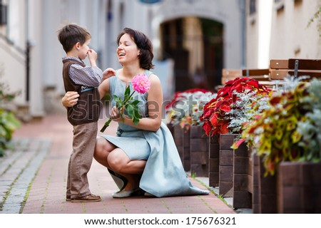 Little boy giving flower to his mom - stock photo