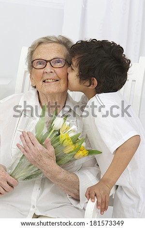 Little boy giving flowers to his grand mother  for, grandmother's day  - stock photo