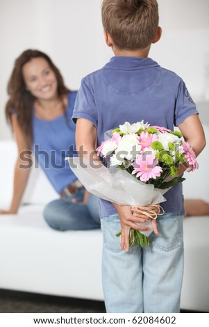 Little boy giving flowers to his mom on mother's day - stock photo