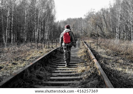 little boy goes deep into the forest along the rails, black and white, left several colors - stock photo