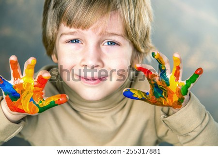 little boy hands painted  in colorful paints - stock photo