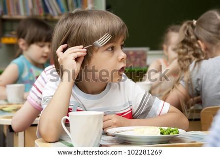 Little boy has a lunch in the kindergarten - stock photo