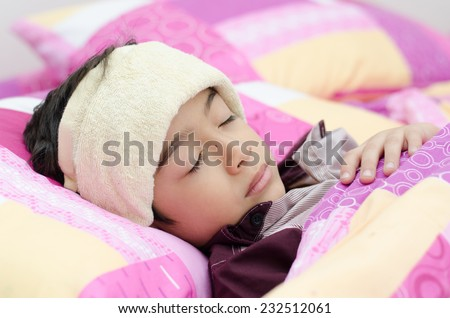 Little boy has fever with towel on head - stock photo
