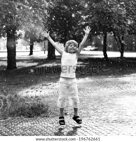 Little boy has fun in the summer rain, black and white