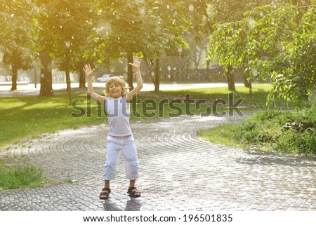 Little boy has fun in the summer rain, toned