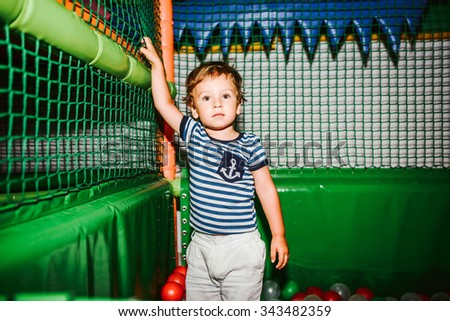 Little boy have fun in the playing room - stock photo
