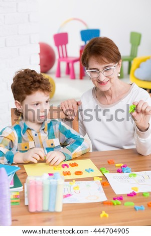 Little boy having a speech therapy session with the use of plastic letters, in a friendly, colorful surrounding