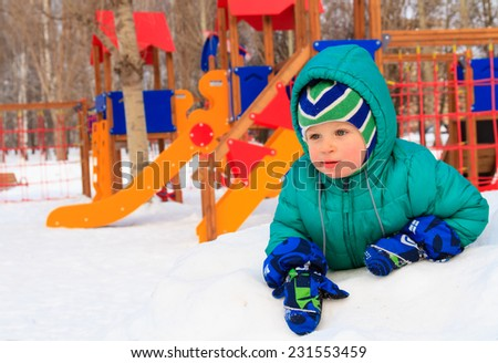 little boy having fun in winter playground outdoors - stock photo