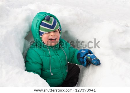 Little boy having fun in winter snow - stock photo