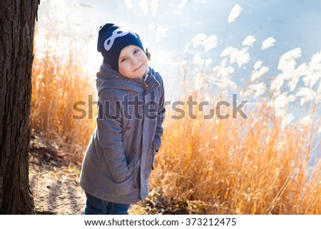 Little boy having fun on the bank of the lake at winter day - stock photo