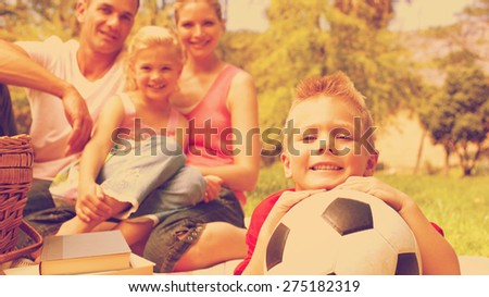 Little boy having fun with a soccer ball with his family smiling - stock photo