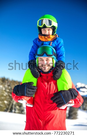 Little boy having fun with his father during skiing in Alps.
