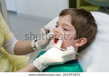 little boy having his teeth checked by dentist - stock photo