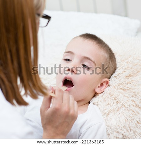 little boy having his throat examined by health professional - stock photo