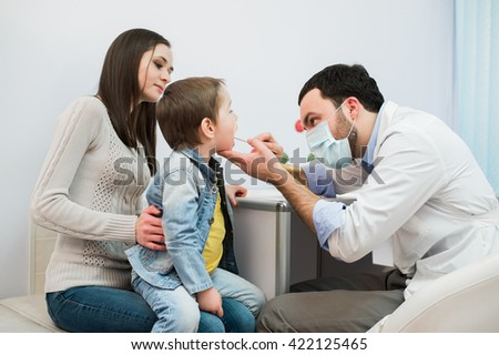little boy having his throat examined by health professional