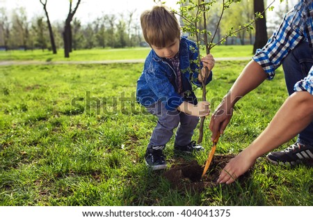 little boy helping his father to plant the tree while working together in the garden. sunday. smiling face.  spring time  - stock photo