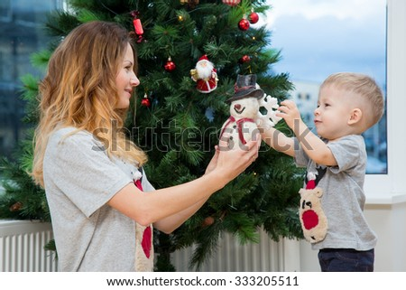 Little boy helping his mom to decorate christmas tree. - stock photo