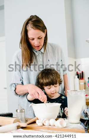 Little boy helping his mother with the baking in the kitchen standing at the counter alongside her kneading the dough for the pie