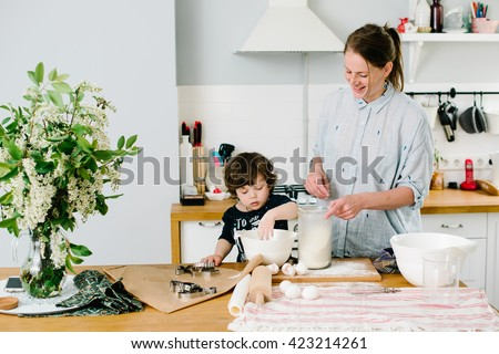 Little boy helping his mother with the baking in the kitchen standing at the counter alongside her kneading the dough for the pie - stock photo