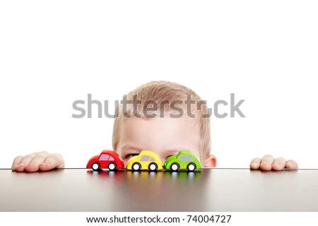 Little boy hiding behind three toy cars - stock photo