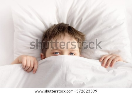 Little boy hiding in bed under the white blanket  or coverlet at home. Sleeping boy. Sleeping child - stock photo