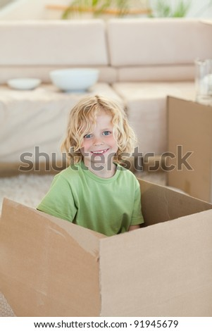 Little boy hiding in cardboard box