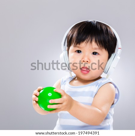 Little boy hold ball and wear headphone