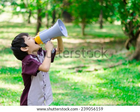Little boy hold megaphone in the park - stock photo