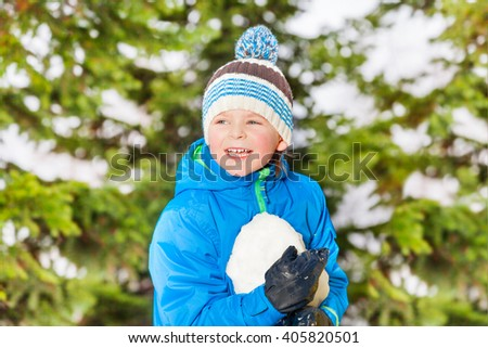 Little boy hold snowball in the winter park - stock photo