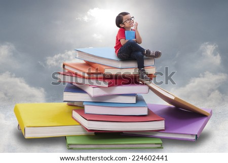 Little boy holding a book and sitting on pile of books  - stock photo