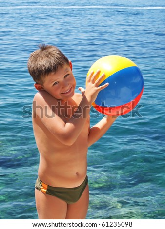 Little boy holding a colorful beach ball by the ocean - stock photo