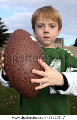 Little boy holding a football, American - stock photo