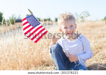 little boy holding american flag and celebrating 4th of July